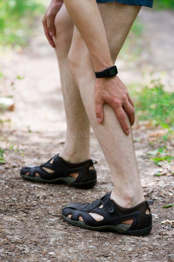 Pijn in kalfsspier, verstuikingen op het been, massage van mannelijke voet, verwonding terwijl het lopen, trauma tijdens training royalty-vrije stock afbeeldingen