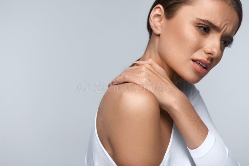 Pijn in Lichaam Mooie Vrouw die Pijn in Hals en Schouders voelen stock fotografie