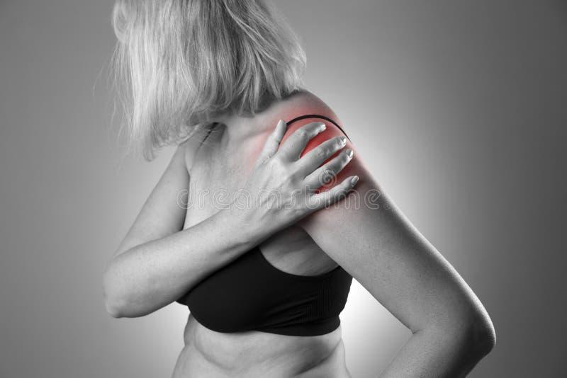 Pijn in schouder, zorg van vrouwelijke handen, pijn in vrouwen` s lichaam stock afbeelding
