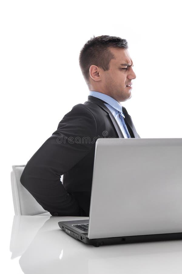 Pijn: zakenmanzitting met rugpijn bij bureau dat op whit wordt geïsoleerd stock foto's