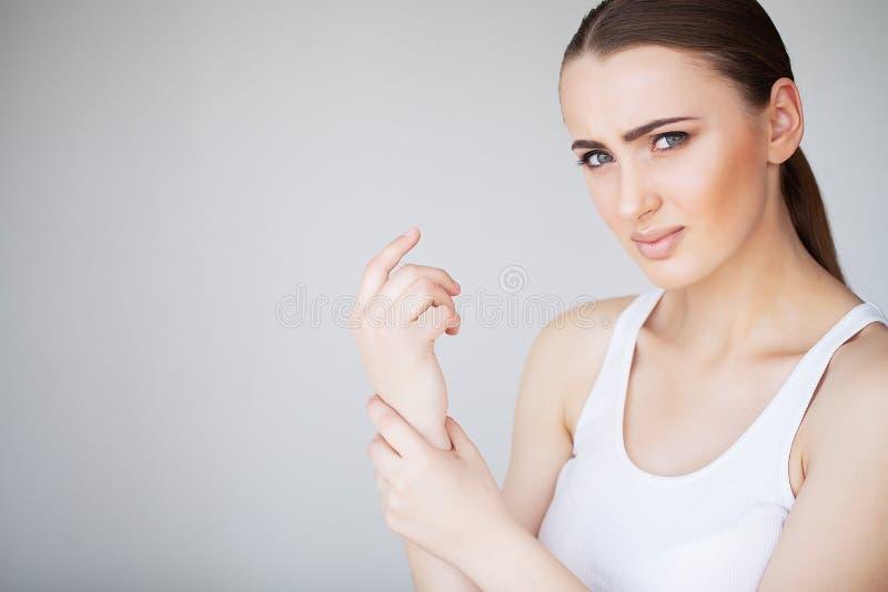 Pijnhand Droevige vrouw met thuis in hand pijn stock fotografie