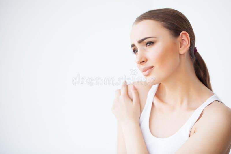 Pijnhand Droevige vrouw met thuis in hand pijn stock foto