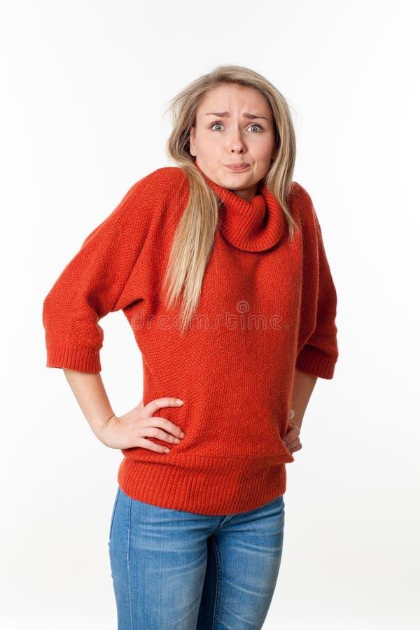 Pijnlijke jonge blonde vrouw die haar schouders voor fout ophalen stock foto's