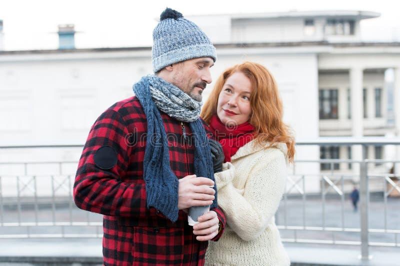 Pijnlijke kerel met koffiekop ter beschikking Het zoete oude paar komt op straat samen Vrouwen tevreden kerel over koffie Het moo royalty-vrije stock afbeelding