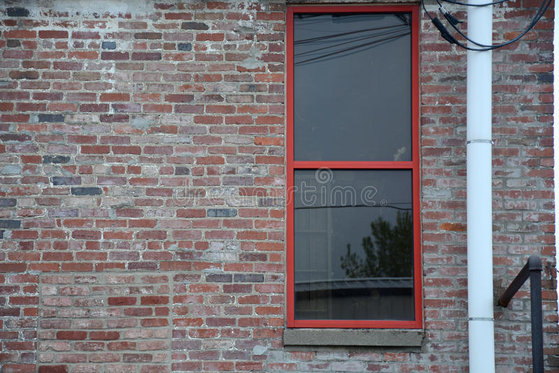Pijp naast rood venster stock afbeelding