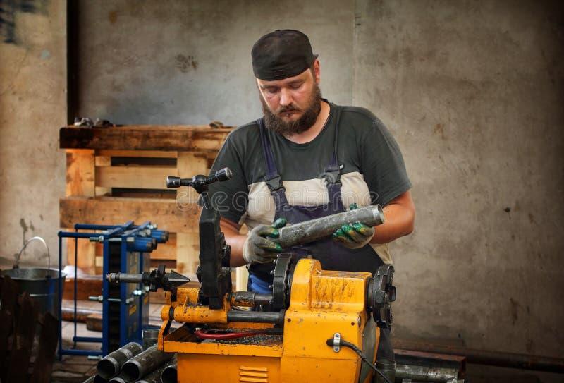 Pijp van het arbeiders de scherpe staal met machine om in te passen stock foto's