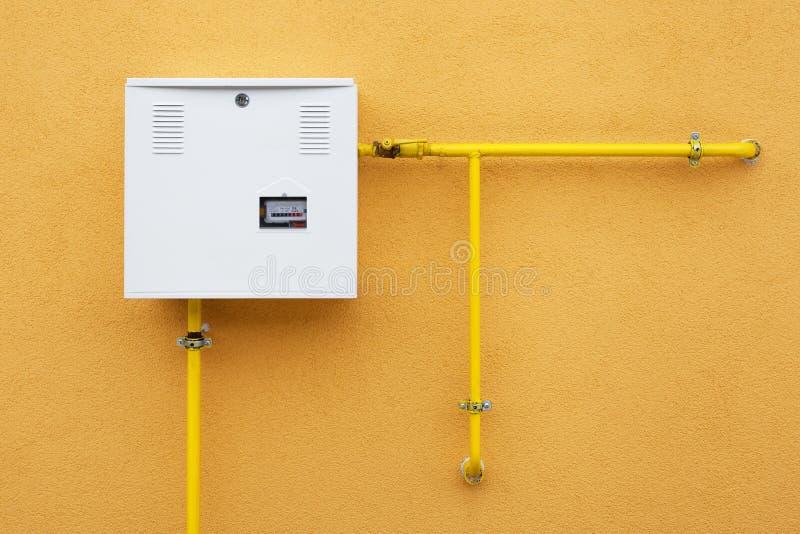 Pijpen en gas-meter op oranje muur stock afbeeldingen