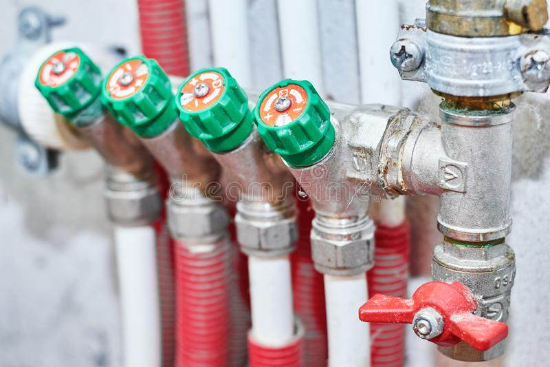 Pijpen en kleppen voor heet en koud water in een het verwarmen en watervoorzieningssysteem stock afbeelding