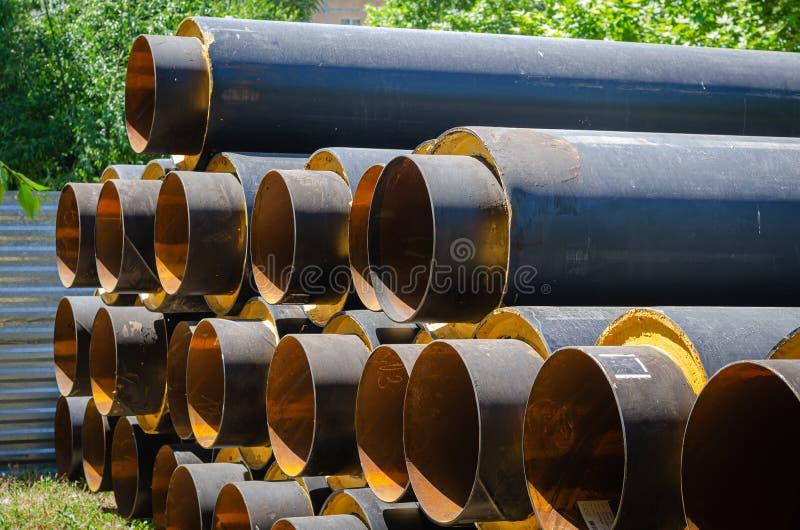 Pijpen voor watervoorziening van grote diameter dichtbij de bouwwerf Het vervangen van oude mededelingen stock fotografie