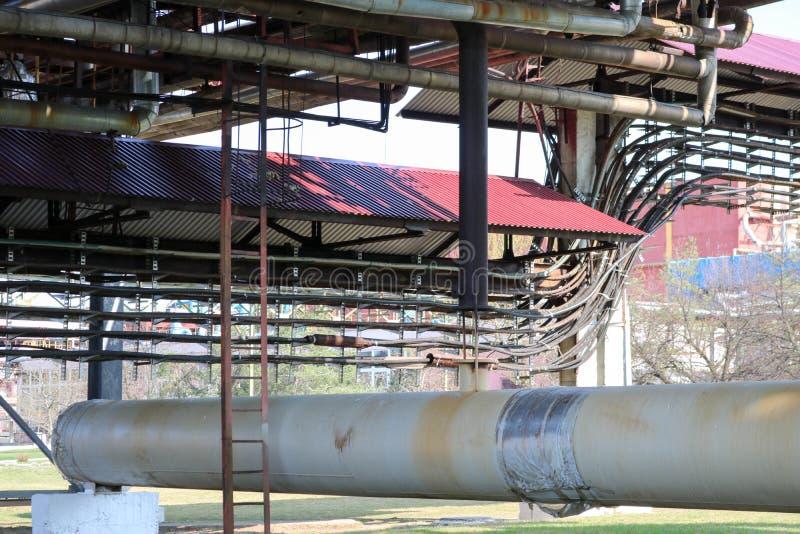 Pijpleidingsviaduct met ijzer roestige pijpen voor het pompen van vloeistof, gecondenseerd met afzet en afvoerkanalen in olieraff royalty-vrije stock afbeelding