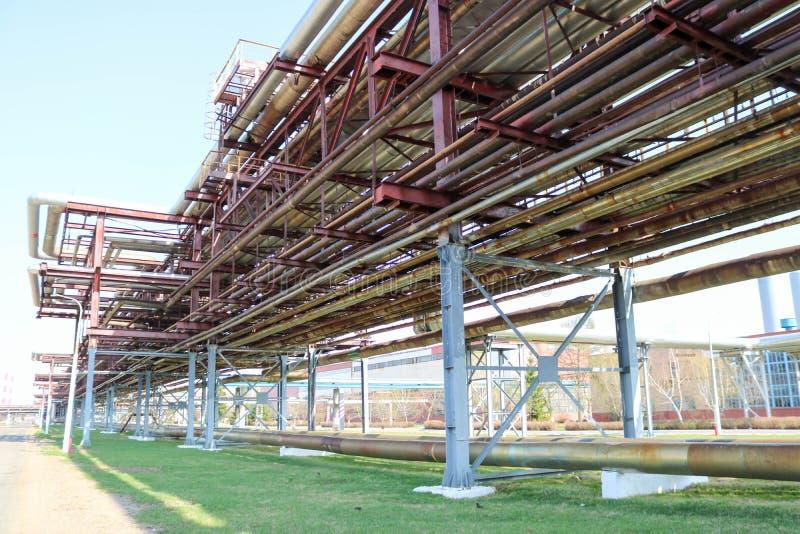 Pijpleidingsviaduct met ijzerpijpen voor het pompen van vloeistoffen met afzet en afvoerkanalen in een olieraffinaderij, chemisch royalty-vrije stock fotografie
