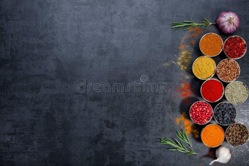 pikantność kolorowe przyprawy Curry, szafran, turmeric, cynamon i otheron, ciemny betonowy tło Pieprz Wielka kolekcja di zdjęcia stock