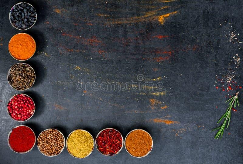 pikantność kolorowe przyprawy Curry, szafran, turmeric, cynamon i otheron, ciemny betonowy tło Pieprz Wielka kolekcja di fotografia stock