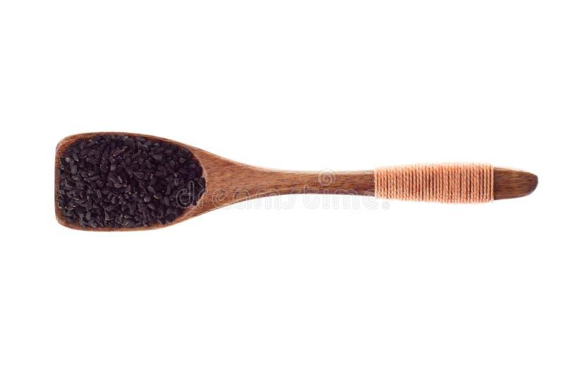 Pikantność Nigella lub Czarni kminów ziarna w drewnianej łyżce odizolowywającej dalej zdjęcie stock
