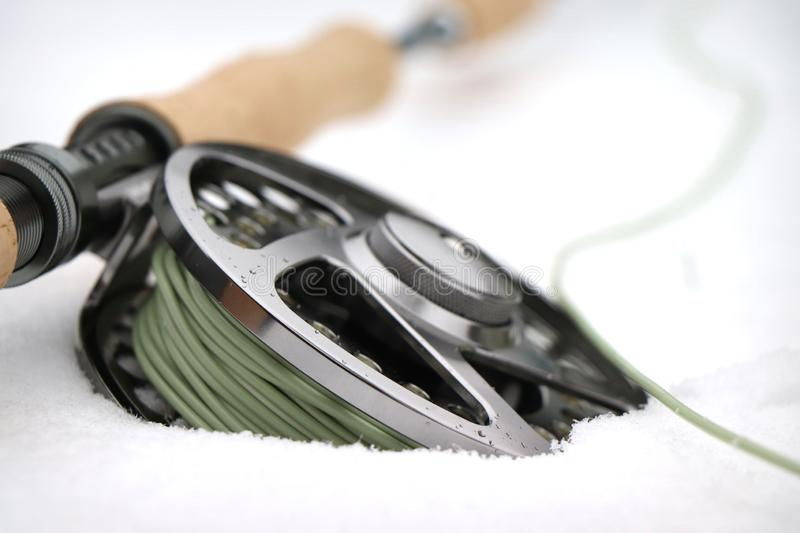 Detail of Fly fishing reel and rod in the snow royalty free stock photos