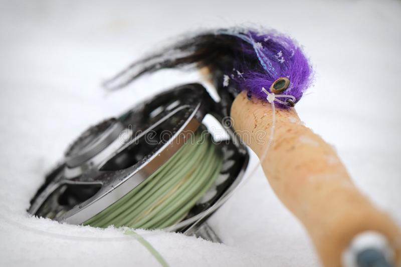 Purple pike fly with fly fishing rod and reel royalty free stock photography