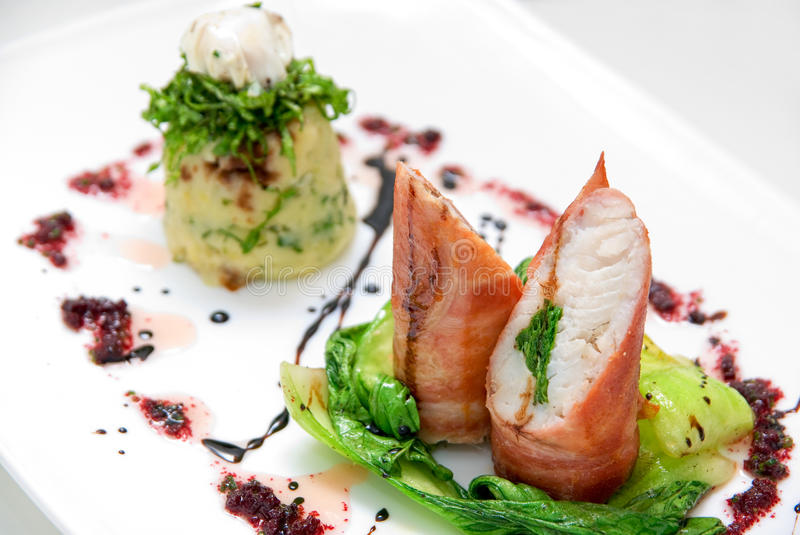 Pike perch at bacon. Tasty dish of pike perch at bacon with basilica, lettuce, dill, parsley, pepper and quail egg royalty free stock photography