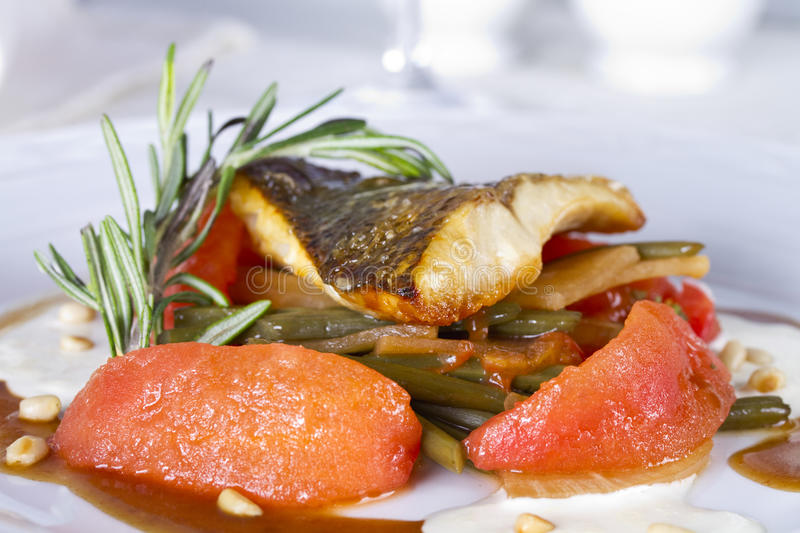 Pike perch fillet baked with arrows of garlic and blanched tomatoes royalty free stock photo