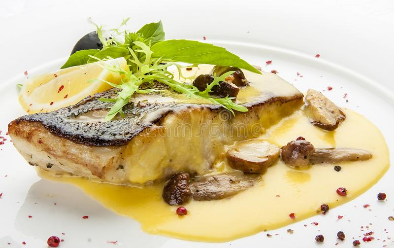 Pike perch with porcini mushrooms and potatoes. On a white plate stock photos