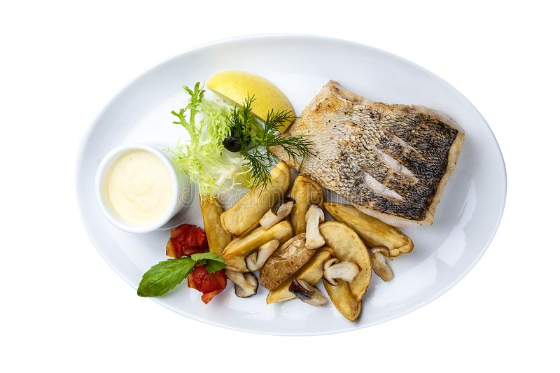 Pike perch with porcini mushrooms and potatoes. On a white plate royalty free stock images