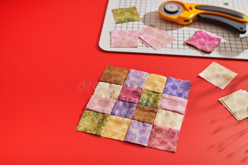 Pikować blok od jaskrawych kwadratowych kawałków tkaniny, obrotowy krajacz, rzemiosło mata, kwadratowi kawałki tkaniny cienie od  obrazy stock