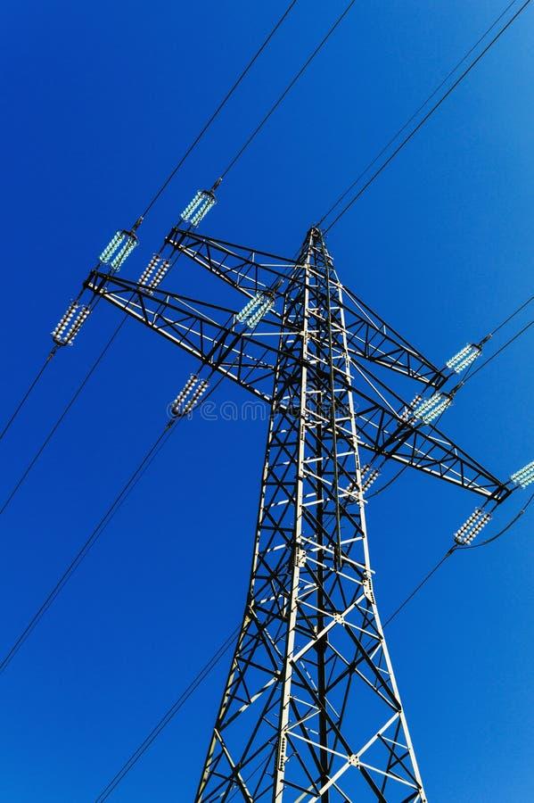 Pilão da eletricidade contra a luz fotografia de stock