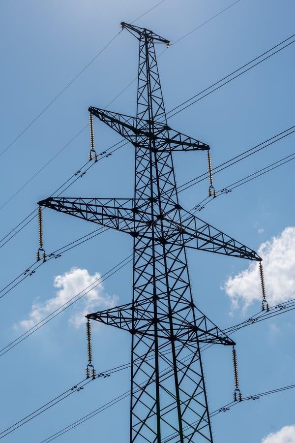 Pilão da eletricidade mostrado em silhueta contra o fundo do céu azul Torre de alta tensão imagem de stock royalty free