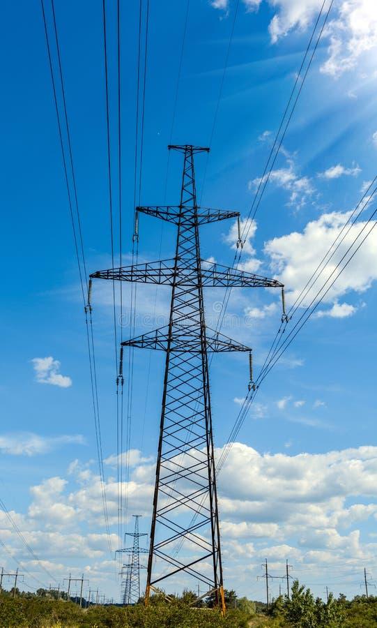 Pilão da eletricidade mostrado em silhueta contra o fundo do céu azul Torre de alta tensão fotos de stock royalty free
