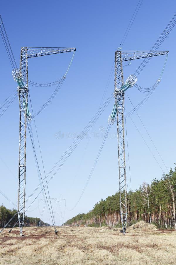 Pilão da transmissão da eletricidade mostrado em silhueta contra o céu azul imagem de stock