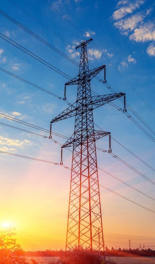 Pilão da transmissão da eletricidade mostrado em silhueta contra o por do sol fotos de stock royalty free