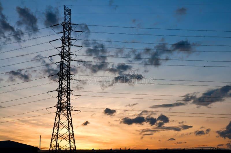 Pilão de alta tensão da eletricidade no por do sol fotos de stock
