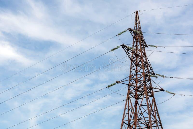Pilón de alto voltaje de la electricidad con el cielo claro azul en fondo Transmisión de la energía imagenes de archivo
