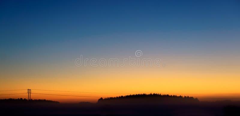 Pilón de la electricidad en el cielo anaranjado foto de archivo