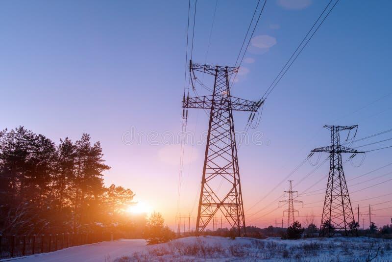 Pilón de la electricidad en un campo con el cielo azul fotografía de archivo