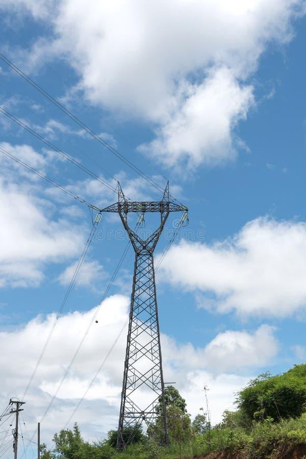 Pilón de la electricidad silueteado contra el cielo azul con backgro de la nube fotos de archivo libres de regalías