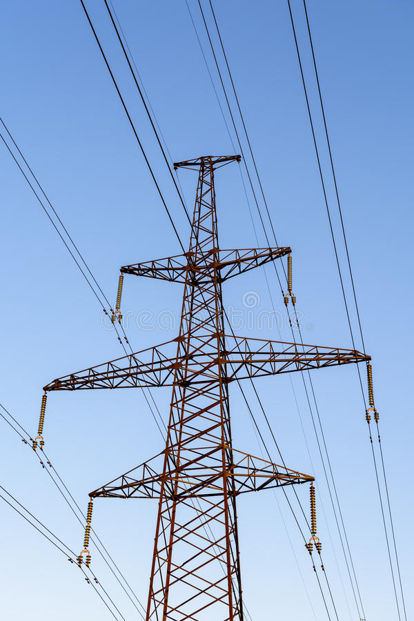 Pilón de la electricidad silueteado contra fondo de la sol del cielo azul Torre de alto voltaje imágenes de archivo libres de regalías
