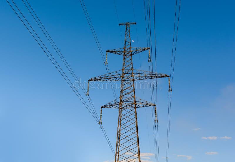 Pilón de la electricidad silueteado contra fondo del cielo azul Torre de alto voltaje fotografía de archivo