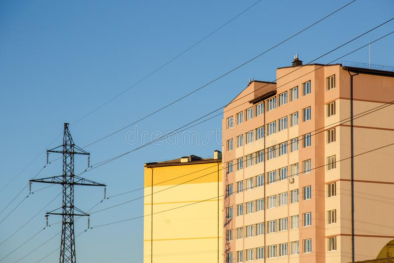 Pilón de la línea eléctrica cerca del edificio residencial de varios pisos foto de archivo libre de regalías