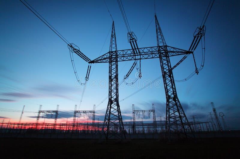 Pilón de la transmisión de la electricidad silueteado contra el cielo azul en d fotografía de archivo libre de regalías
