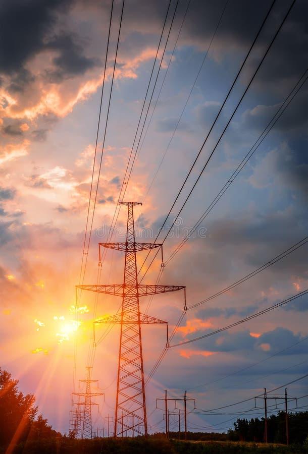 Pilón de la transmisión de la electricidad silueteado contra el cielo azul en la oscuridad fotos de archivo libres de regalías
