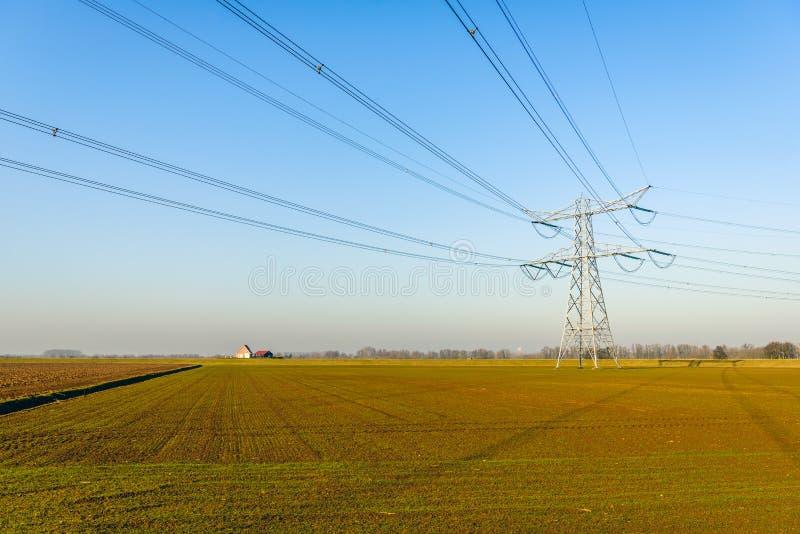 Pilón y cables de alto voltaje en un paisaje plano fotos de archivo