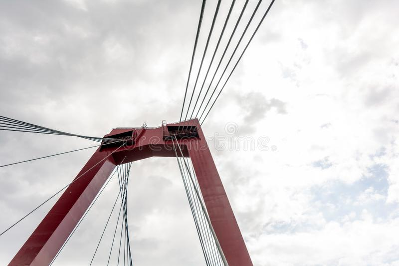 Pilón y cables rojos del puente de Willemsbrug contra el cielo nublado imagen de archivo libre de regalías
