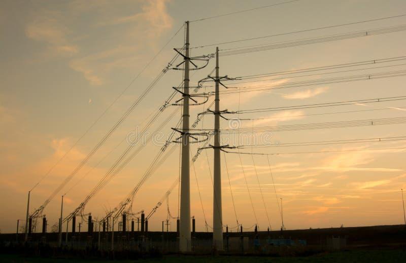 Pilões da eletricidade com fundo alaranjado imagens de stock royalty free