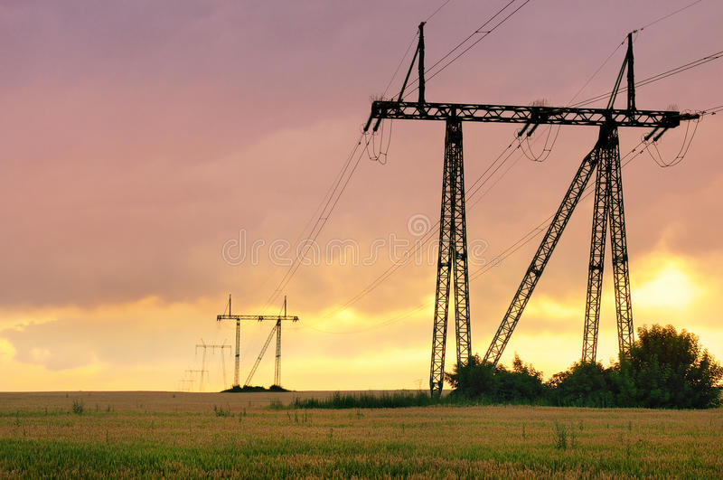Pilões da energia eléctrica no por do sol fotos de stock