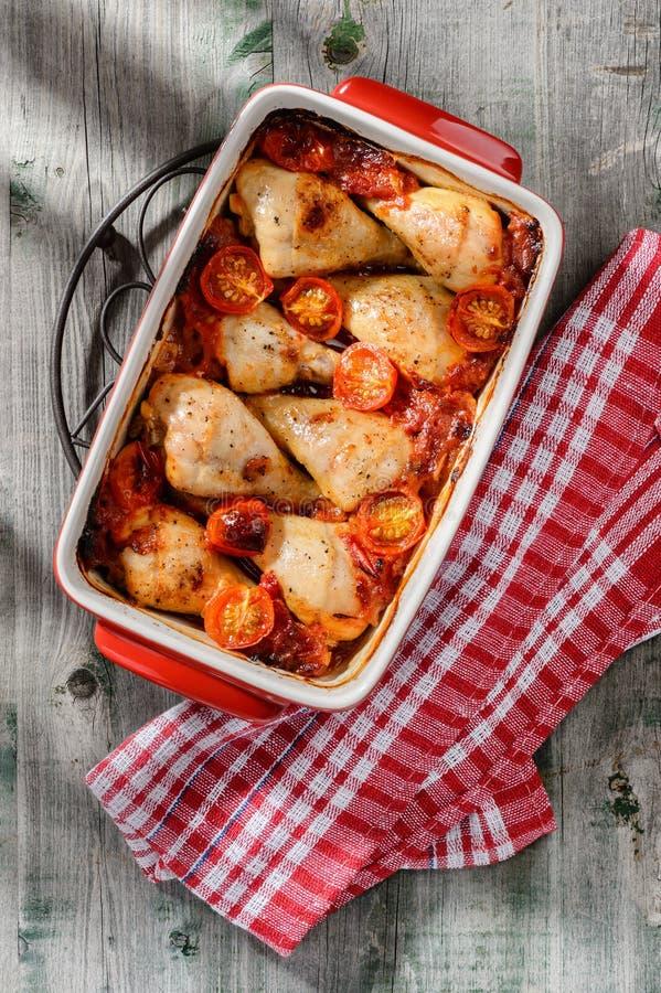 Pilões de galinha cozidos no molho com tomates, cebola e garli foto de stock royalty free