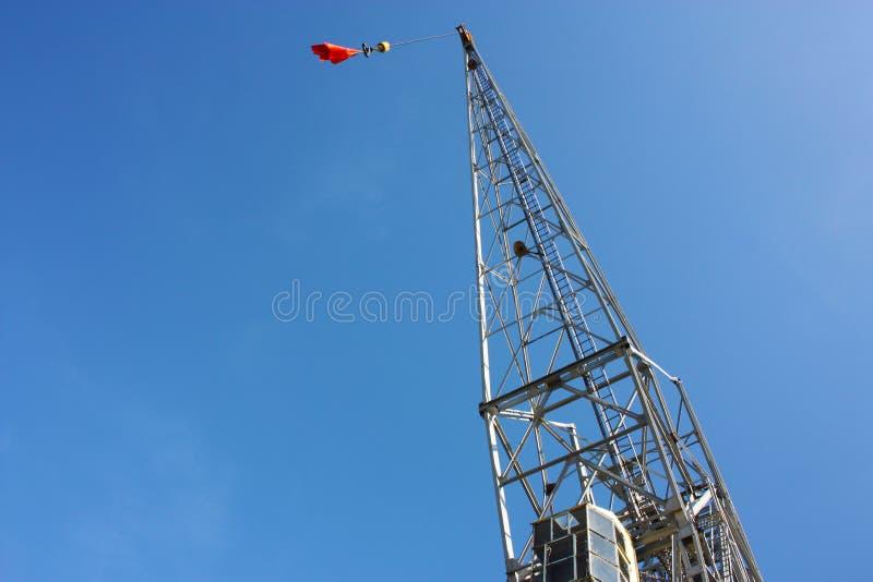 Pilões do andaime estrutura industrial alta do metal em que uma bandeira vermelha desconhecida é içada o céu é claro - azul imagens de stock