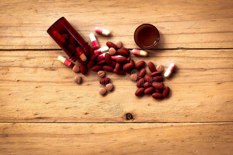 Pil die uit de bruine fles van de kleurenpil op oude houten backgro morsen royalty-vrije stock foto