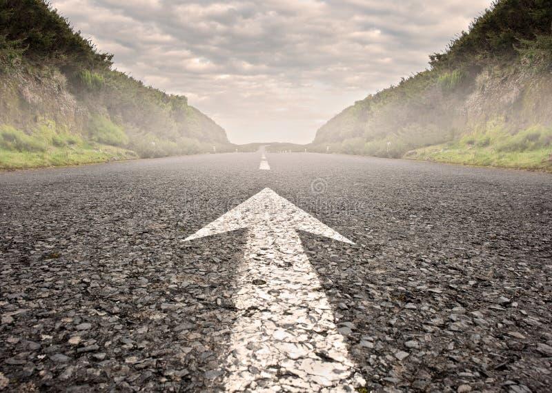 Pil på asfaltvägen arkivbild