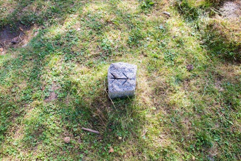 Pil som huggas på en sten för att signalera en slinga för trekking eller lantligt cykla på gräset royaltyfria foton