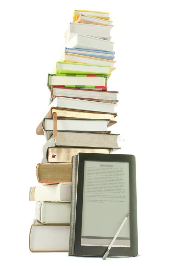 Pila alta de libros y del programa de lectura del e-libro fotografía de archivo